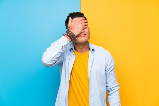 Hombre joven sobre ojos que cubren coloridos aislados por las manos