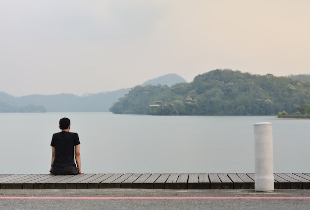 Hombre joven solo que se sienta en la calzada de madera que mira a la montaña en el lago con puesta del sol