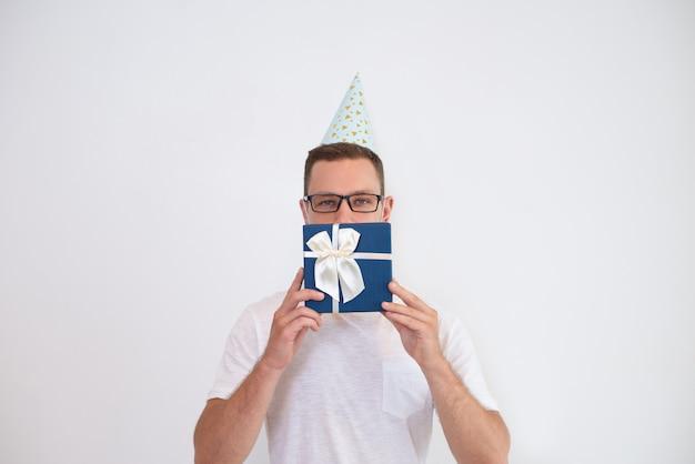 Hombre joven en sombrero de fiesta que cubre la boca con caja de regalo