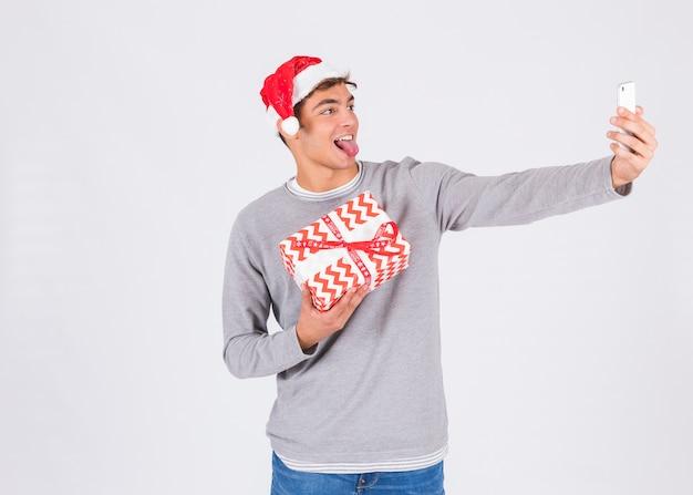 Hombre joven en sombrero de navidad con teléfono inteligente y caja actual