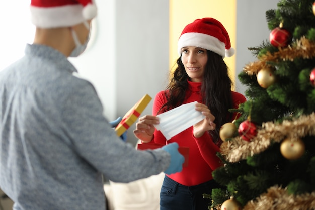 Hombre joven con sombrero de santa claus dando regalo a la mujer mascarilla protectora cerca del árbol de navidad en casa