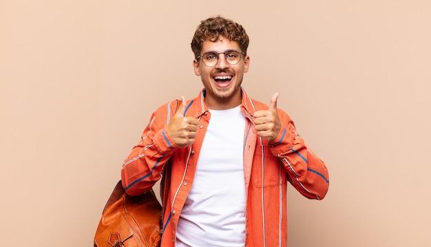 Hombre joven sonriendo ampliamente, feliz, positivo, seguro y exitoso, con ambos pulgares hacia arriba. concepto de estudiante