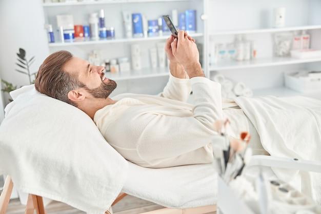 Hombre joven sonriendo y sosteniendo el teléfono inteligente mientras espera el procedimiento cosmético en la clínica de cosmetología estética.
