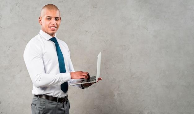 Hombre joven sonriente acertado que usa el ordenador portátil que mira a la cámara que se opone a la pared gris