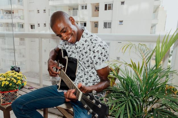 Un hombre joven sonriente africano que se sienta en silla en el balcón que goza tocando la guitarra