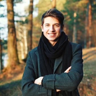 Hombre joven sonriente con los brazos cruzados al aire libre