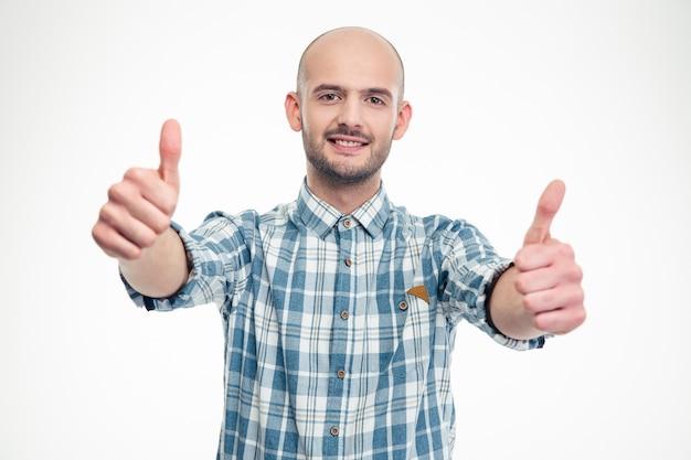 Hombre joven sonriente confiado en camisa a cuadros que muestra los pulgares hacia arriba con ambas manos sobre la pared blanca