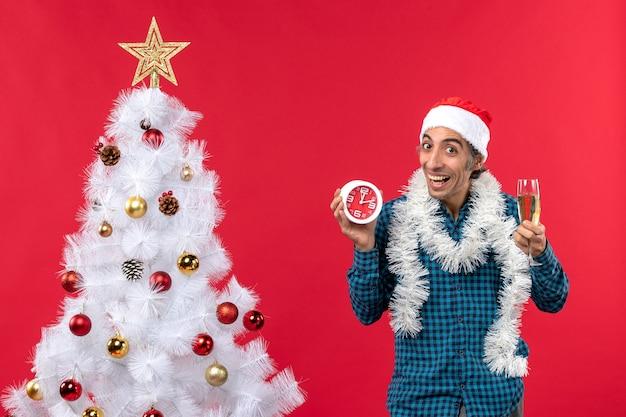 Hombre joven sonriente confiado con sombrero de santa claus y sosteniendo una copa de vino y reloj de pie cerca del árbol de navidad