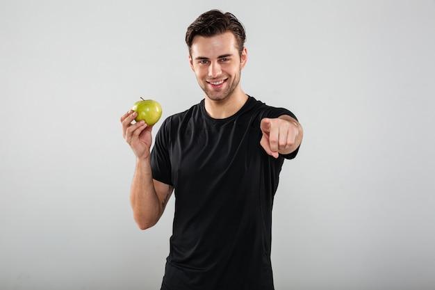 Hombre joven sonriente de los deportes que sostiene la manzana que le señala.
