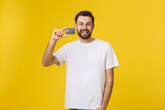 Hombre joven sonriente feliz que muestra la tarjeta de crédito aislada en amarillo