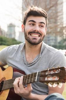 Hombre joven sonriente hermoso que toca la guitarra en al aire libre