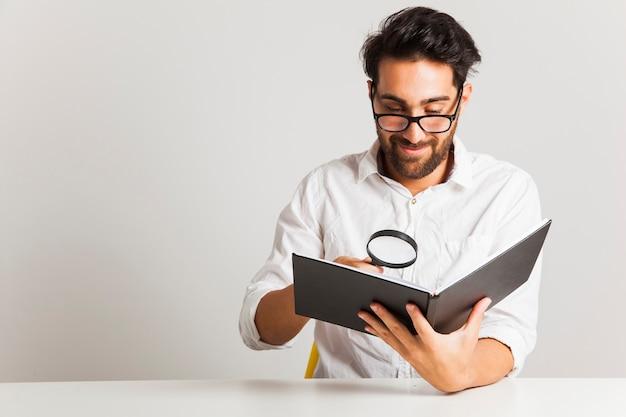 Hombre joven sonriente leyendo con lupa