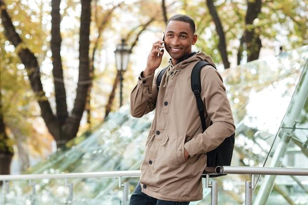Hombre joven sonriente con mochila hablando por su teléfono en la calle