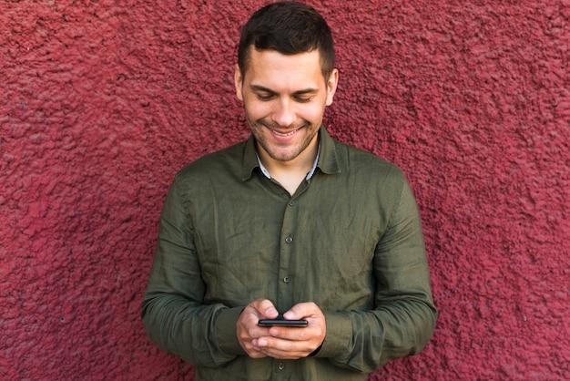 Hombre joven sonriente ocupado en mensaje de texto a alguien