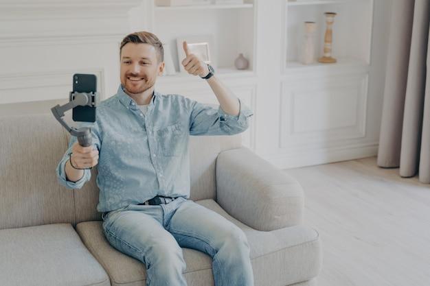 Hombre joven sonriente positivo vestido con ropa casual que muestra los pulgares para arriba gestos en el chat de video, sosteniendo el teléfono usando el cardán, sentado solo en el sofá beige en la sala de estar temática de luz