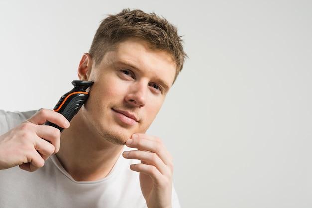 Hombre joven sonriente que afeita con la máquina aislada en el fondo blanco