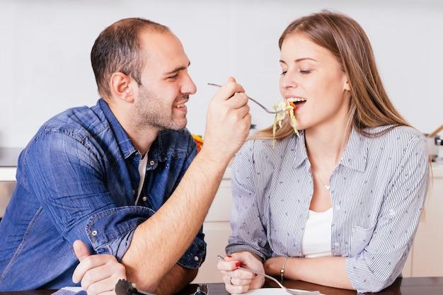 Hombre joven sonriente que alimenta la ensalada a su esposa con la cuchara