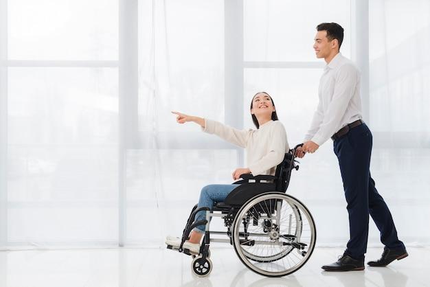 Hombre joven sonriente que ayuda a una mujer joven que se sienta en la silla de ruedas que señala su finger en algo