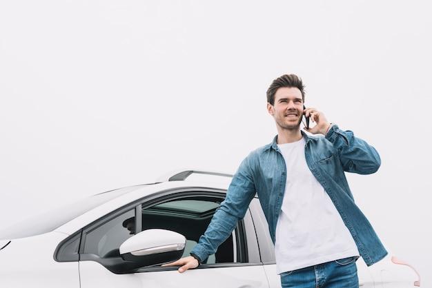 Hombre joven sonriente que se coloca delante del coche que habla en smartphone