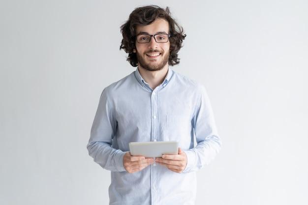 Hombre joven sonriente que coloca y que sostiene la tableta