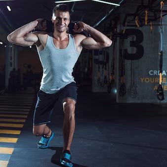 Hombre joven sonriente que hace entrenamiento en gimnasio