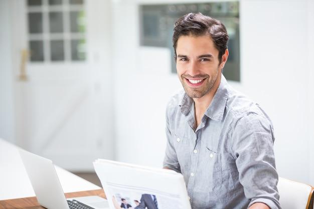 Hombre joven sonriente que lleva a cabo documentos mientras que se sienta en el escritorio con la computadora portátil