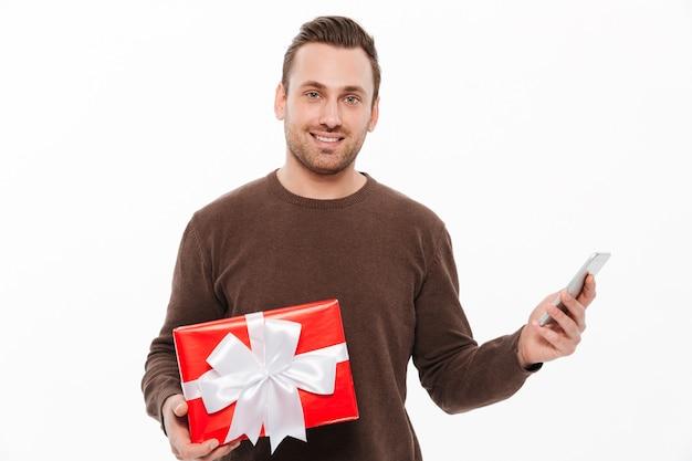 Hombre joven sonriente que lleva a cabo sorpresa de la caja de regalo.