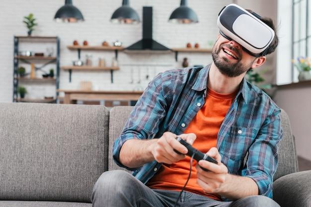 Hombre joven sonriente que lleva las gafas de la realidad virtual que se sientan en el sofá que juega al videojuego
