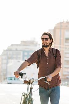 Hombre joven sonriente que lleva las gafas de sol que caminan con la bicicleta en el camino por tarde