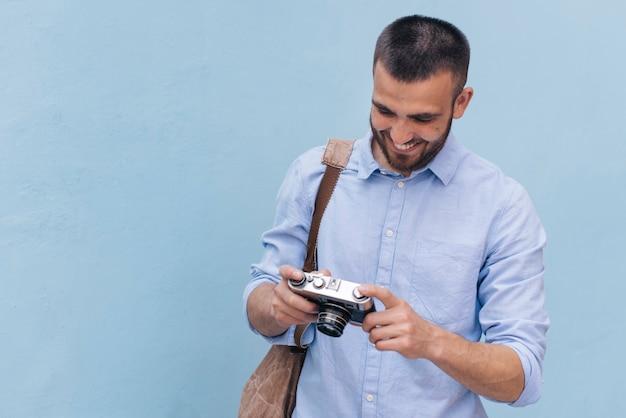 Hombre joven sonriente que lleva la mochila y que mira la cámara que se coloca cerca de la pared azul