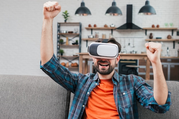 Hombre joven sonriente que lleva la realidad virtual google que aprieta su puño