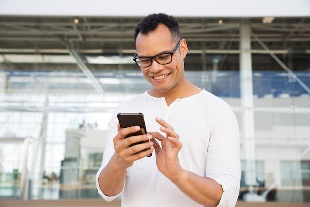 Hombre joven sonriente que manda un sms en smartphone al aire libre