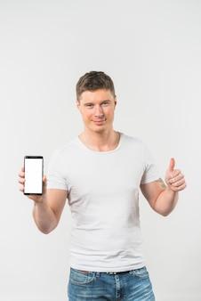 Hombre joven sonriente que muestra el pulgar encima de la muestra que muestra el teléfono elegante contra el fondo blanco