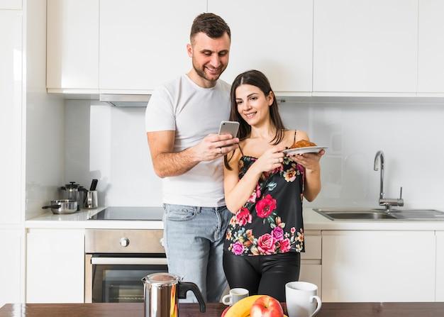 Hombre joven sonriente que muestra a su novia algo en el teléfono móvil en la cocina