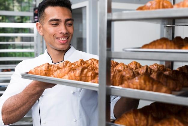 Hombre joven sonriente que quita la bandeja del croissant de la hornada del estante
