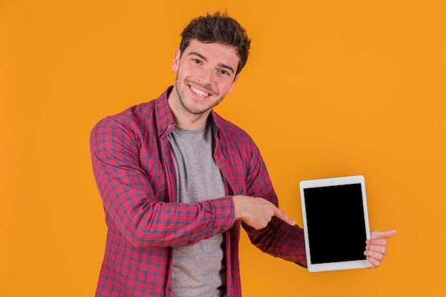Un hombre joven sonriente que señala su dedo en la tableta digital contra un fondo anaranjado