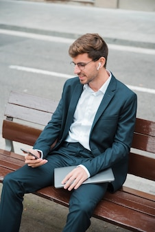Hombre joven sonriente que se sienta en el banco sobre la calle usando el teléfono móvil con el auricular inalámbrico