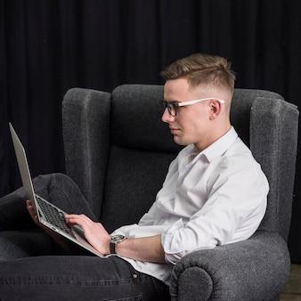 Hombre joven sonriente que se sienta en la butaca usando el ordenador portátil