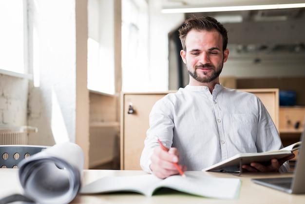 Hombre joven sonriente que se sienta en la silla que trabaja en oficina