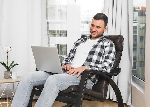 Hombre joven sonriente que se sienta en silla usando el teléfono móvil en casa