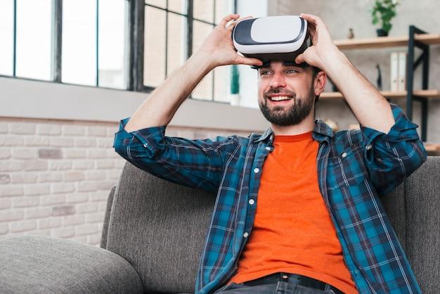 Hombre joven sonriente que se sienta en el sofá que lleva la cámara de la realidad virtual