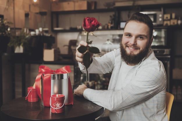 Hombre joven sonriente que sienta la tabla que sostiene una rosa