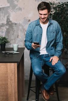 Hombre joven sonriente que se sienta en taburete usando el teléfono móvil en casa