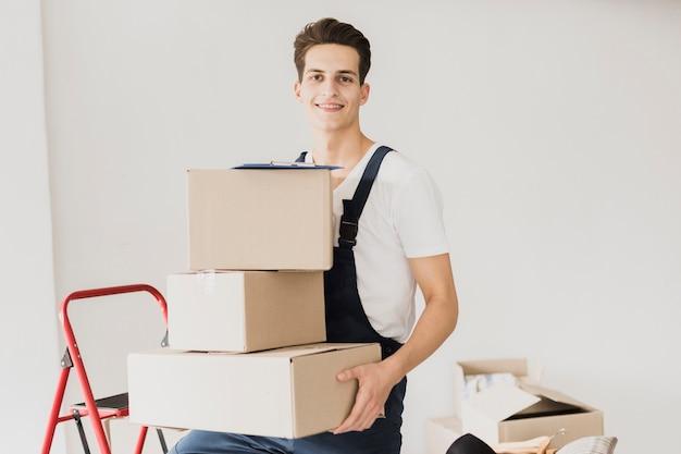Hombre joven sonriente que sostiene las cajas de cartón