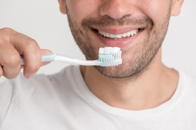 Hombre joven sonriente que sostiene el cepillo de dientes con pasta