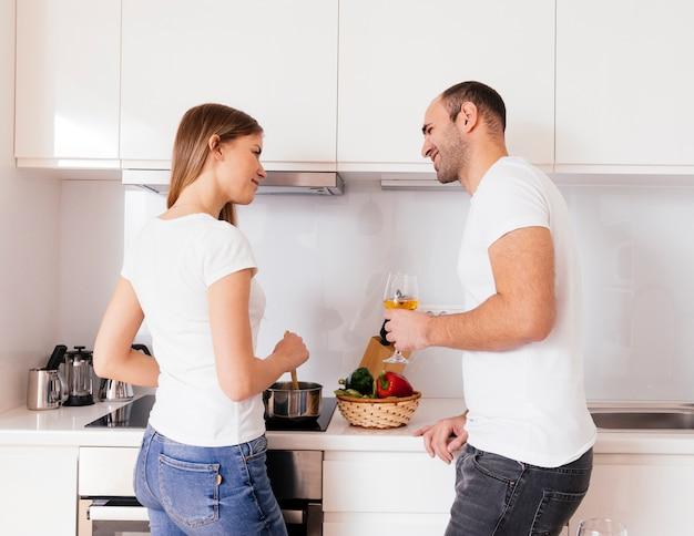 Hombre joven sonriente que sostiene la copa en la mano que mira a su esposa que prepara la comida en la cocina