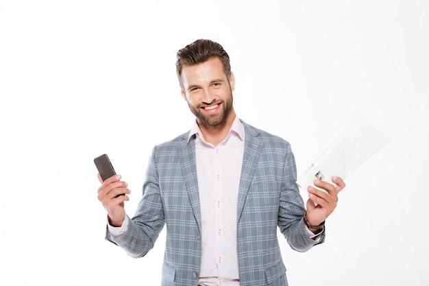 Hombre joven sonriente que sostiene la gaceta y el teléfono móvil.