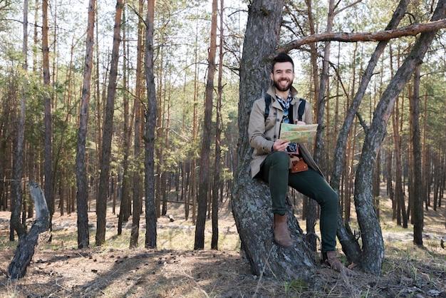 Hombre joven sonriente que sostiene el mapa en la mano que se sienta debajo del árbol en el bosque