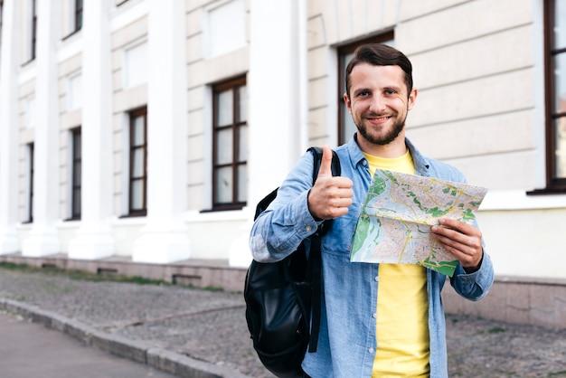 Hombre joven sonriente que sostiene el mapa y que muestra el pulgar encima del gesto en el aire libre