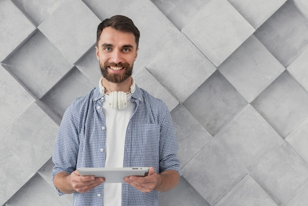 Hombre joven sonriente que sostiene la maqueta de la tableta